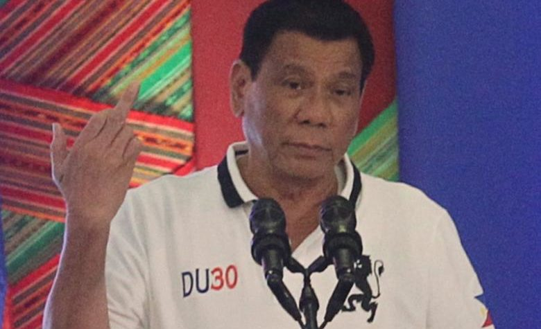 Philippine President Rodrigo Duterte raises a middle finger thrust out in an obscene gesture as he speaks before local government officials in Davao